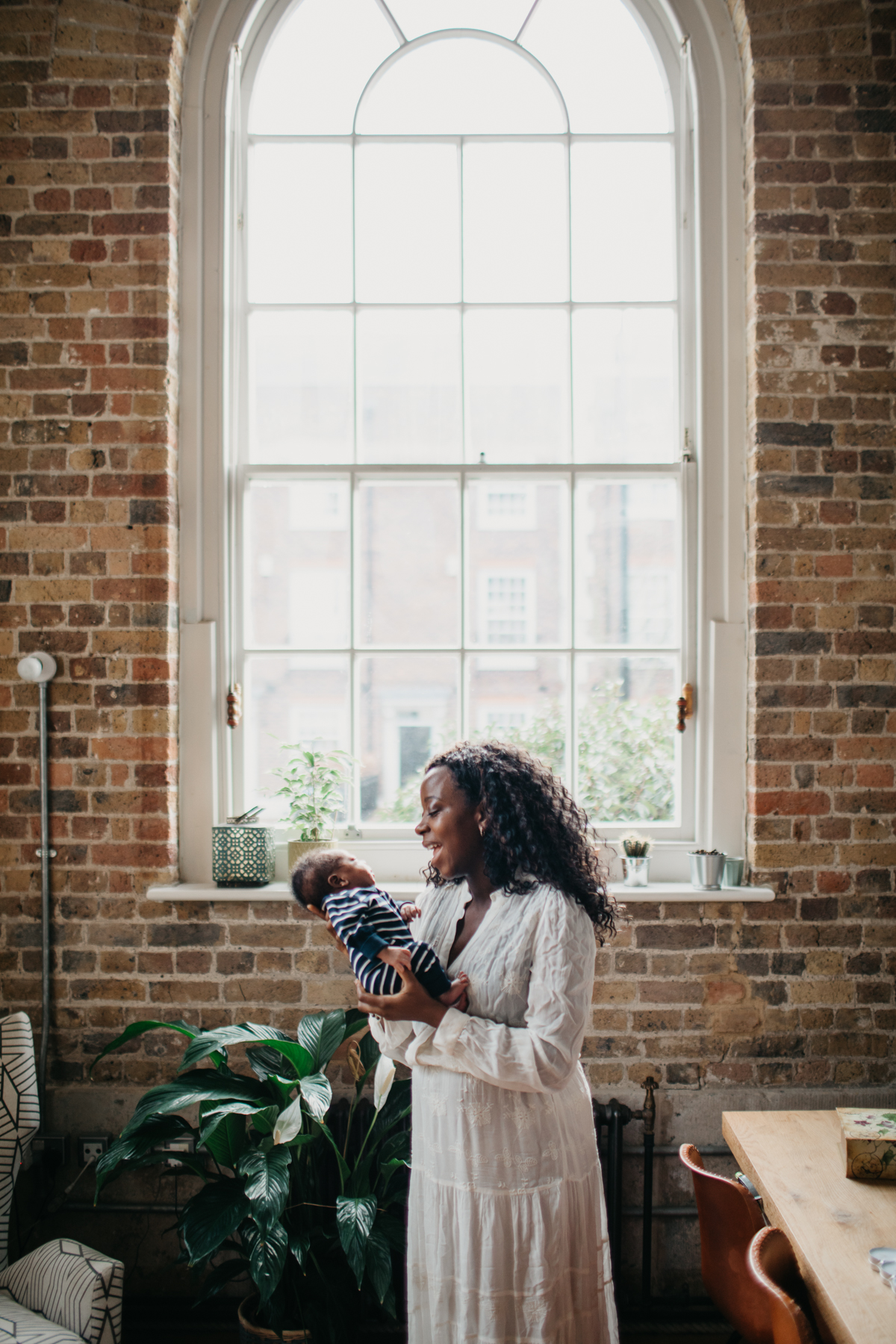mother holding newborn by large window